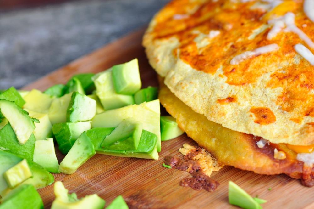 Sliced avocado beside a veg enchilada